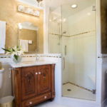 vanity-built-in-custom-chandelier-master-bathroom-antique-wood-cabinet-wallpaper-master-bath