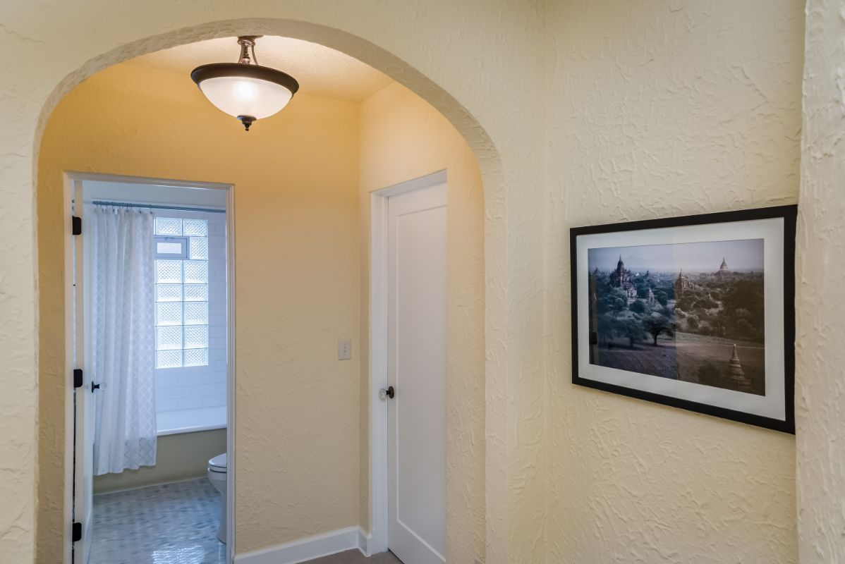 textured-plaster-arched-hallway-white-painted-woodwork-Tudor-home-Whitefish-Bay